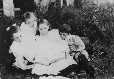 800px-StateLibQld_2_125327_Group_of_children_sitting_on_the_grass_reading_books,_1900-1910